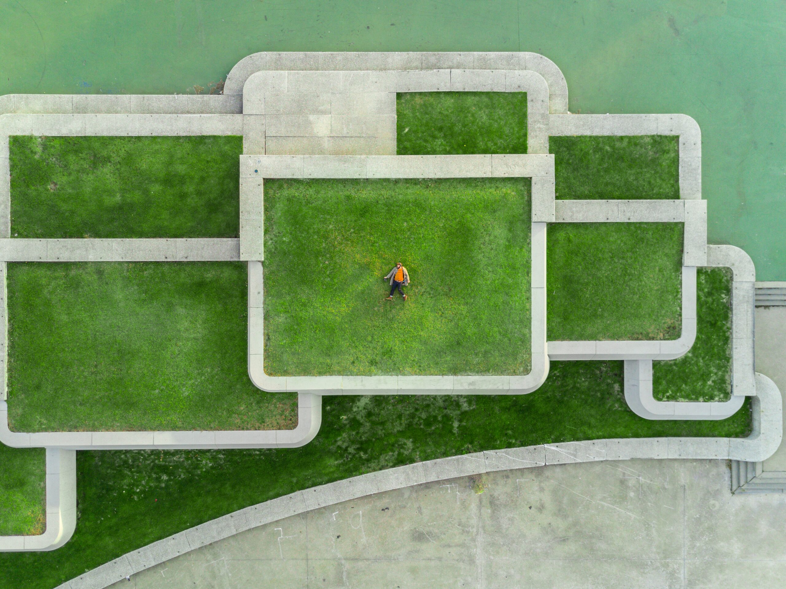 Man laying down in field or maze.