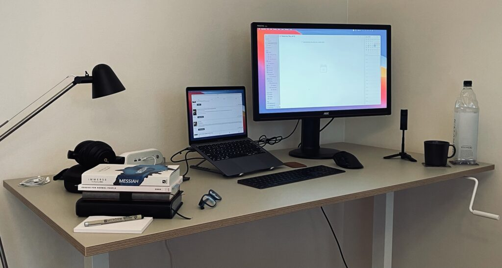 My standing desk setup in my home office consists of an IKEA standing desk frame, table top, MacBook, a stand for it, as well as an external monitor, keyboard, and mouse.